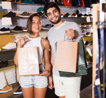 happy italian  adult male and female with purchases in paper bag in the boutique
