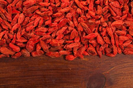 Closeup of dried goji berries on dark wooden background. Concept of healthy eating