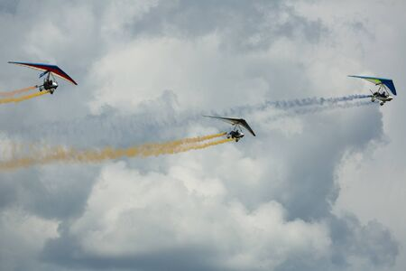 Ultralight trikes performing in sky with colored smoke on air show