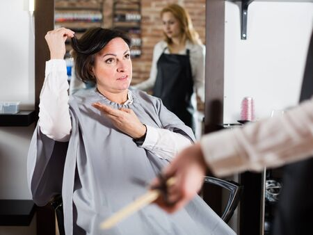 Mature woman is upset by her haircut and master in hairdressing salon