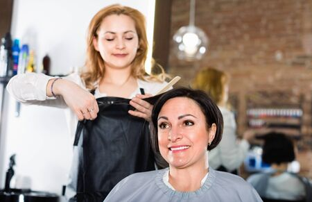 Young smiling cheerful  hairdresser does to woman haircut with use of scissors and hairbrushes in hairdress salon