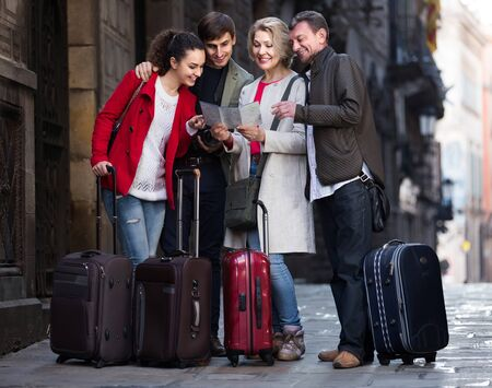 Portrait of  smiling european tourists with map and baggage seeing the sights in European city