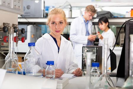 Young positive female student working in university laboratory, writing report on results of chemical experiments in notebook