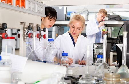 Two girls students of Faculty of Chemistry performing experiments in university laboratory, recording results in workbook