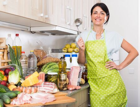 Portrait of cheerful female who is readying for cooking new recipe at home.