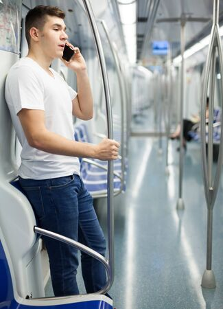 Portrait of young confident man in white shirt traveling on subway and talking on smartphone