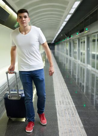 Young male passenger in casual clothing with baggage walking on platform of metro station Standard-Bild