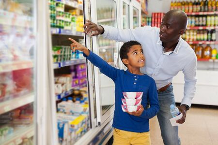 cheerful adult African American man with his little son making purchases together in grocery