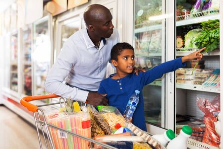 Focused African tween boy helping his father choose fresh vegetables in grocery store. Focus on man Foto de archivo
