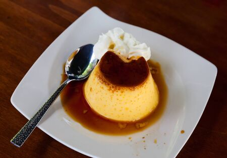 Popular Spanish custard dessert flan with layer of caramel sauce and whipped cream