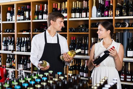 Seller man wearing apron helping to buy bottle of wine to woman customer in wine store Imagens