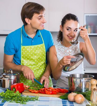 Happy russian man and woman standing near table with vegetables Archivio Fotografico
