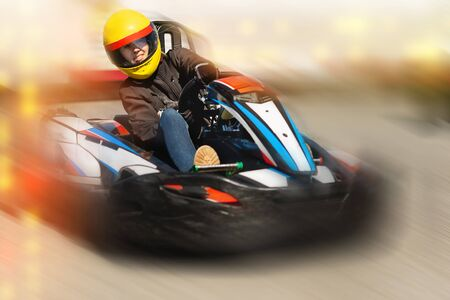 Portrait of girl in helmet driving kart at the racing track outdoors