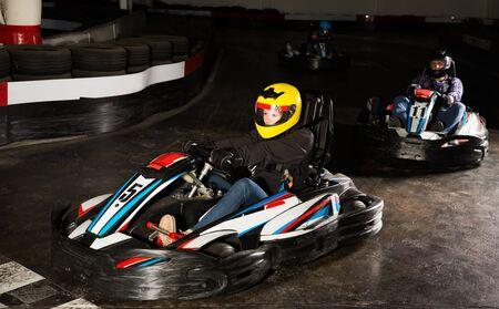 Portrait of young woman driving racing car at kart circuit