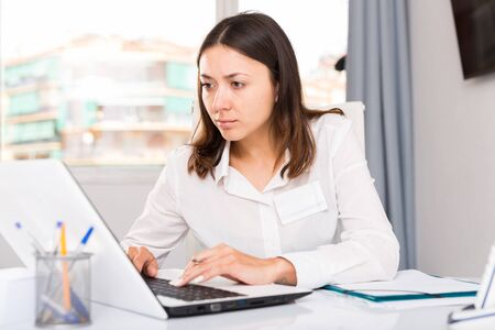 Young  woman  working with laptop and papers at the office  table