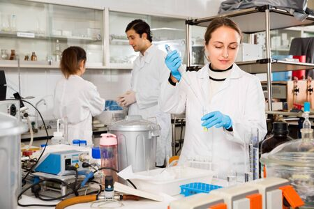 Diligent  positive female student performing experiments in university laboratory, using mechanical lab pipette for mixing chemicals