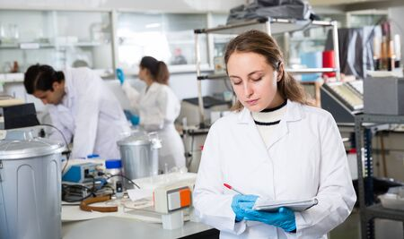 Young female scientist making research in chemical laboratory and taking notes in test chart