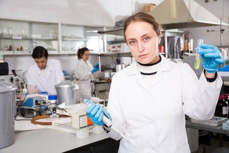 Professional female chemist working in laboratory, analyzing liquid samples in test flasks