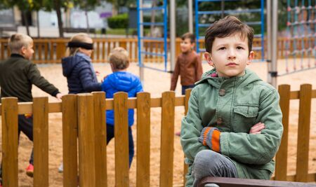 Portrait of offended upset boy not playing with friends after quarrel on playground