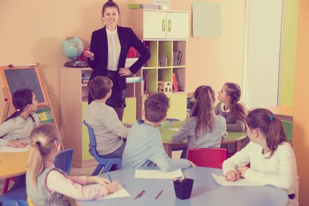 Elementary age group of pupil  listening teacher and sitting  at class
