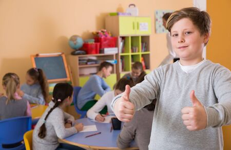 Smiling schoolboy hold thumbs up near children drawing at class