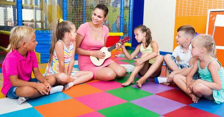 Cheerful kids listening positive teacher playing small guitar at education class