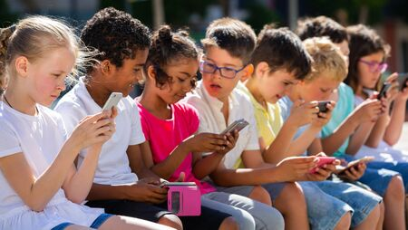 Group of smiling children sitting at urban street with mobile devices