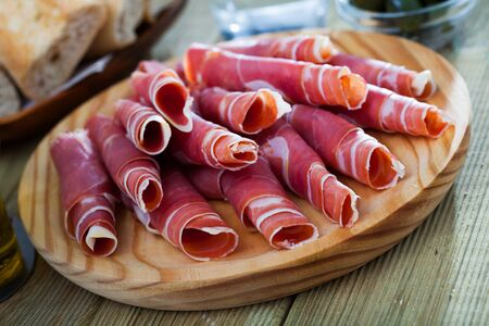 Delicious Spanish dry cured jamon served as rolls on wooden plate