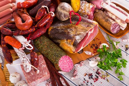 Display of mince, sausages and meat with spices on table Фото со стока