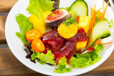 Colorful salad with raw tuna, greens, cucumbers, mango, figs, carrot, radish and kumquat Banque d'images
