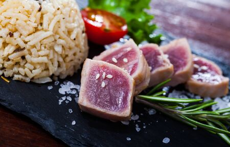 Appetizing slightly roasted tuna with boiled rice and fresh vegetables