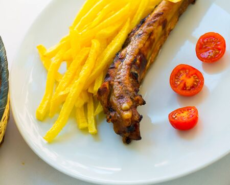 Portion of barbecued pork ribs with french fries and fresh tomatoes