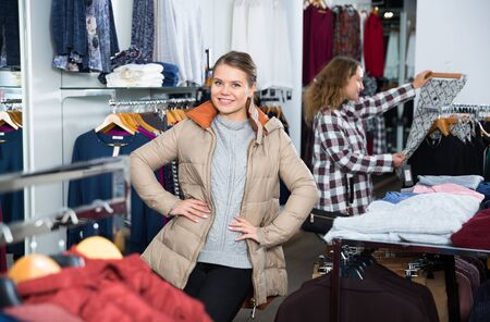 Portrait of happy woman posing wearing coat in clothing store Stockfoto