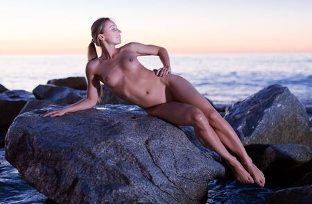 Nude young happy woman is lying on a rock near the sea at the dawn.