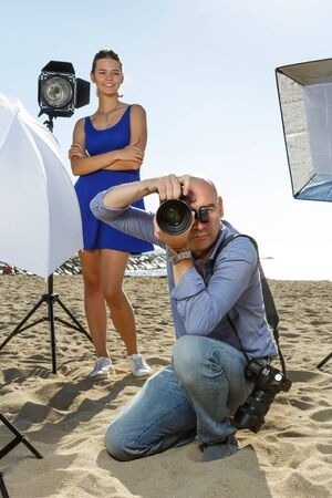Male photographer with large professional camera looking into viewfinder and taking pictures on seaside Imagens