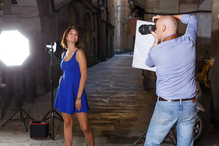 Cheerful woman in blue dress posing for professional photographer on old city street