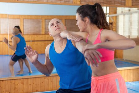 Active woman with professional trainer are training captures on the self-defense course in gym Stok Fotoğraf