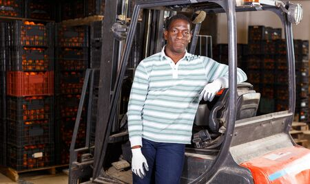 Portrait of confident positive African American man standing near forklift at fruit warehouse