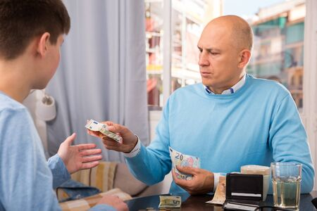Father giving cash his late teens son for daily expenses