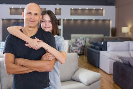Happy husband and wife posing in room with sofas in furniture shop