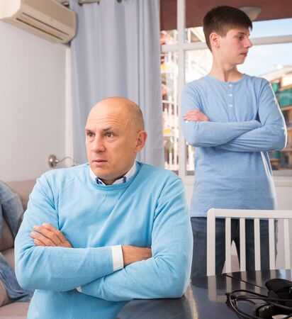 Portrait of offended father after quarrel with son sitting at home