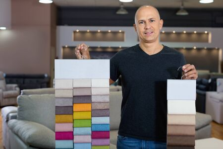 Portrait of  positive  man showing various samples of textures for furniture in shop