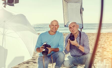 Portrait of two positive photographers with cameras among professional photo equipment on sea shore Imagens - 127702768