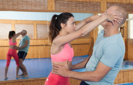 Ordinary female is fighting with trainer on the self-defense course for woman in sport club Stock Photo