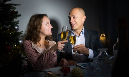 Happy couple drink champagne and watch TV on Christmas night Stock Photo