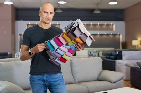 Portrait of glad positive smiling man holding and choosing samples of upholstery fabric in furniture salon