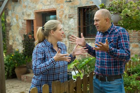 Worried woman standing behind wooden fence near farmhouse, having unpleasant talk with male neighbour Imagens