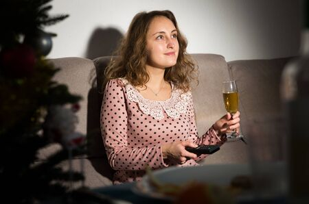 Happy young woman watching TV on Christmas night