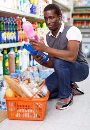 calm African man holding bottle of household chemicals in big store