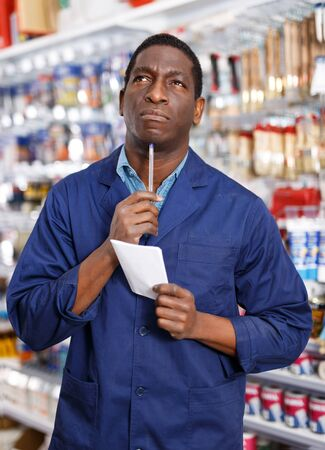 Serious African American worker taking inventory of goods in building materials store Imagens